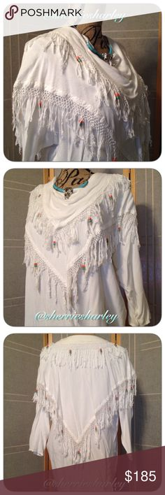 """Boho Beaded White Poncho Drape-Style Moroccan Hand made in Morroco, this beautifully beaded top is stunning. Coral & Turquoise colored beads and white hand made fringe layers over a scoop neck long sleeve, longer tunic style top. 65% Cotton. 35%Rayon. Brilliant white for those special occasions. Armpit to Armpit 25"""" across flat. Waist 25"""" across. Hips 25"""" across. Shoulder to front hem 28"""". Shoulder to back hem 30"""" for a beautiful hi-low tunic with poncho style tiers on both front and back…"""
