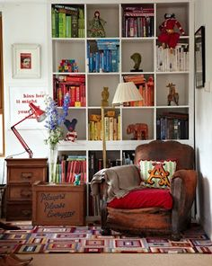 color coded book nook! Especially love having a chair in front of the shelf