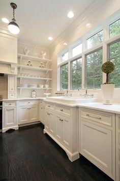 "Beautiful white kitchen by Oxford Development. Carrara marble, white subway tile, integrated appliances, dark oak floor, and Kohler's 48"" Harborview sink with double Rohl faucets."