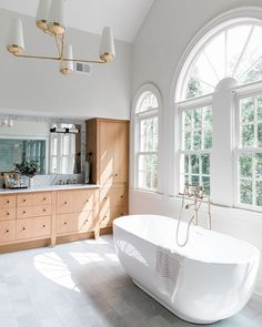 Expansive windows and a warm oak vanity adorned with Top Knobs hardware in Flat Black creates a open and spaccious setting in this master bathroom. Knobs And Handles, Clawfoot Bathtub, Cabinet Hardware, Kitchen And Bath, Master Bathroom, Floor Plans, Vanity, Windows, Warm