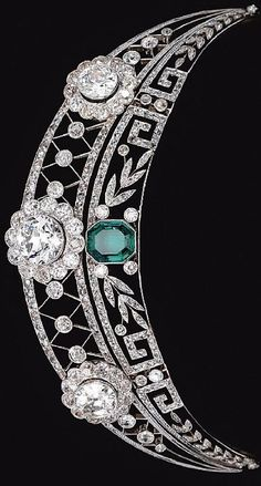 Emerald and Diamond Tiara, dirca 1910. The upper tier of open work trellis design millegrain-set throughout with rose diamonds, and decorated with three flower head cluster motifs set with circular-cut diamonds, the lower tier of foliate and meander design, set with similarly-cut stones and centring on an octagonal emerald.