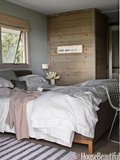 """In Harriet Maxwell MacDonald and Andrew Corrie's Shelter Island, New York beach house, the warm wood walls were sanded and covered in a diluted wash. """"We kept all the fabrics to natural, muted tones, and it's all the colors you see in the view – whites, grays, blues, a bit of pale pink,"""" MacDonald says. White bed linens look even more crisp and fresh when they're paired with wood."""