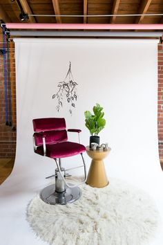 A vintage barber chair, reupholstered in raspberry velvet and a shag rug make this a great area for filming or hanging out!