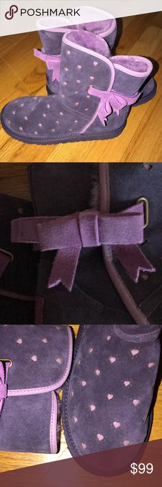 UGG Australia Tie Bow with Purple Hearts Beautiful plum boot with lighter Purple Heart cut outs. Now sits above ankle bone on the outside of the boots. NEVER WORN! children's size 3 fits women's 5.5 or 6. UGG Shoes Slippers