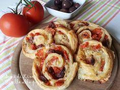 Iniziamo la preparazione delle gustose Girelle alla pizza, tagliando i pomodori e la mozzarella a cubetti piccolissimi. Tagliare le olive nere in 4 parti.