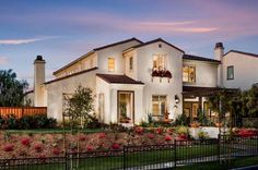 White stucco, red Spanish tile, trellis and window box add character to this San Diego-area new home. The Serenity Model, Stonebridge Estates Community, Brookfield Homes.