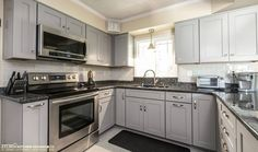 This modern Waypoint kitchen uses maple cabinets in a Painted Stone finish and beautiful exotic Blue Pearl GT granite countertops. Visit https://www.zelmarkitchendesigns.com/ for more design ideas.  Grey Shaker Cabinets; white glass subway tile backsplash