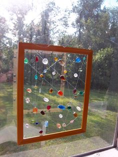 Colorful glass beads strung on fishing line in a yellow, wooden frame. Frame is approximately 8.5x11. Topped with an accented hanging loop, I will include an extra length of fishing line so it can be easily hung where it will catch the most light. A delightful accent to brighten any space. Makes a great housewarming or office-warming gift.    All materials in this project are upcycled.    I am happy to ship internationally; please contact me for rates.    (I dont feel like these photographs…