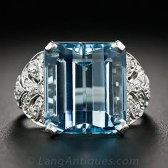 Art Deco Aquamarine and Diamond Ring in Platinum. A cool, deep glacier-blue emerald-cut aquamarine, measuring 10 carats, brightly glistens above and between a pair sparkling diamond-set plaques, adorned with decorative pierced details and fine milgraining, in this consummate Art Deco and smile-inducing jewel, crafted in platinum - circa 1930s.