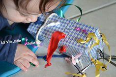 Bébé (6 mois) aime beaucoup les ficelles, cordes, et tout ce qui dépasse. Petite création maison : la boîte à rubans ! Simple et efficace.