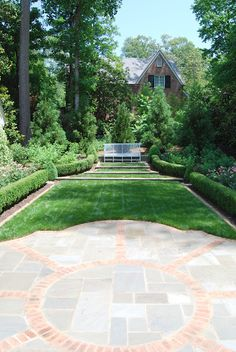 Beautiful combination of hardscape and lush green lawn on four narrowing levels in a formal garden.