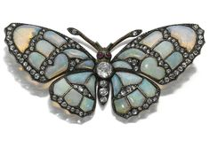 OPAL, RUBY AND DIAMOND BROOCH. Designed as a butterfly, set with opal and rose diamonds, the eyes accented with rubies cut en cabochon.