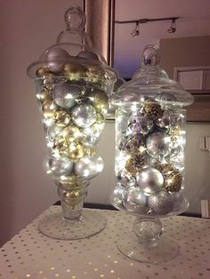 apothecary jars with silver & gold ornaments, bells, pine cones, and fairy lights #apothecaryjars #christmas #decor #fairylights #ornaments #silver #gold
