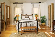 In the master bedroom, gray damask linens add subtle color and pattern to the iron-and-brass bed. To coordinate, draperies made of silver-and-gray fabric were lined in white.