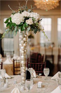 Centro de mesa rellenode bolas de navidad y decorado en la parte superior con flores para ambientación de boda en temporada navideña. #BodasNavidad