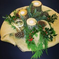 Louri's beautiful diy centerpieces. Navy blue tablecloth topped with burlap. Woodsy decor with: pine cones, greenery, candles made out of logs, mason jars with floating candles and river rocks at the bottom and finally a tealight candle wrapped with twigs! Repin!