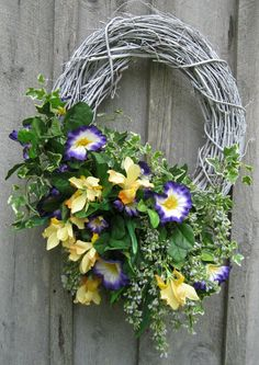 Gorgeous purple & white morning glories & buttery yellow daffodils overflow with lush greens & vines on this beautiful grapevine wreath!