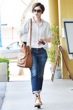 Lily Collins wears a pin-striped oversized button-up, blue boyfriend jeans, tan sandals and a brown bucket bag.