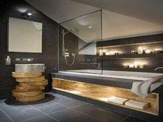 salle de bain zen sous pente. Plan vasque en rondins de bois, niche encastrée et carrelage gris anthracite ajoutent une note cosy à la pièce