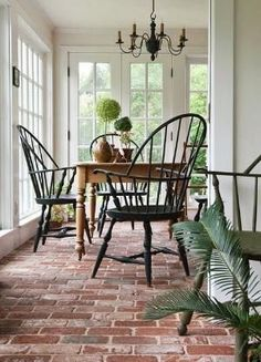 Brick floors in the sun porch help create an indoor-outdoor flow. - Traditional Home ® / Photo: Kendra Clineff