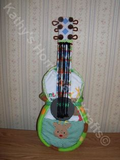 this guitar is sure to be the hit of the baby shower, especially if the mom or dad to be are a guitar player.Perfect for any music lover. The body is made with approximately 40 size 1 pampers and covered in a new with tags Christmas Outfit size 0-3M. The body of the guitar is wrapped with a fleec...