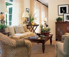 """""""It has an easy, carefree quality,"""" the designer says of the loggia, which connects to the living room. A 19th-century Anglo-Indian cabinet is at right, below Ellen Graham's photographs of John Wayne and model Corpo. Henry Calvin sofa fabric. Coraggio drapery fabric. Stark carpet."""