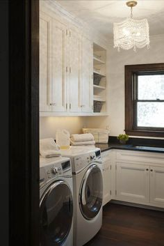 Beautiful laundry room with custom white cabinetry accented with nickel and crystal cabinet pulls alongside black counters which frame an undermount sink situated below a sash window with dark stained trim.