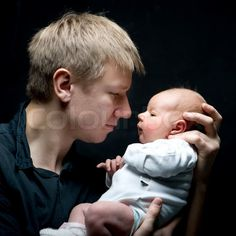 Stock image of 'Portrait of a young father and his newborn baby daughter'