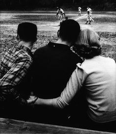 Photographer/Creator  Tom Walters  Collection  1959  Publisher  Charlotte Observer  Caption/Description  Photograph of a girl sitting with her boyfriend at the baseball game. She has her arm around him and is holding the hand of a boy sitting on the other side of her boyfriend.