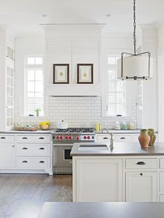 Gorgeous, crisp and clean kitchen. I love the detailed molding and the transom windows.