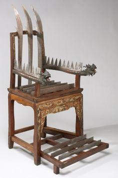 Chaise de torture en bois. Une dizaine de lames dans chaque bras, plus trois sous les pieds. Made in China
