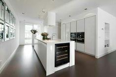 Moderne keuken in hoogglans wit met een strakke donkere vloer.