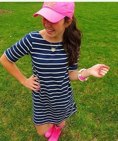Striped shift, glossy Hunters, a baseball cap, and a necklace.