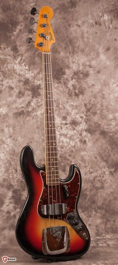 1966 Fender Jazz Bass, Sunburst. This gorgeous bass features a body only authentic period correct 3 tone Sunburst refinish in nitro lacquer by Fiesta Finishes™. The pick guard is a Fender Vintage r...