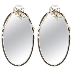 Pair of mirrors, each having an oval beveled mirror plate, in painted iron frame, with rope details, surmounted by silver gilt iron bow, draped with ribbons.