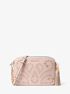 The Ginny crossbody strikes the perfect balance between understated and luxe, with a lightly structured and compact design that's embellished with dome studs and eyelet details in a whimsical motif. Finished with chain-link accents and an oversized tassel, this bohemian-inspired style is an easy way to elevate any outfit.