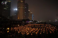 People hold candles during an event attempting to establish a Guinness World of Record for Blowing out the most number of candles simultaneously during Earth Hour in Shanghai. CARLOS BARRIA/REUTERS