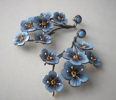 Kolczyki na sztyft wykonane ze srebra 930 i skóry naturalnej. Kwiaty niezapominajek namalowane ręcznie wodoodporną i odporną na ścieranie farbą w odcieniach błękitu wykończone dekoracyjnymi żyłkami. Srebro oksydowane na kolory brązu i złota. Całkowita długość kolczyka łącznie z zawieszką wynosi 6,5 cm  KOLCZYKI DOSTĘPNE NA ZAMÓWIENIE