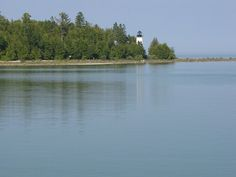 The old Presque Isle Lighthouse seen arcoss the Harbor Pier; Presque Isle, MI