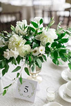 White wedding ideas, white and greenery wedding, white boutonnieres, ranunculus boutonnieres, white centerpieces, white wedding centerpieces, cherry blossom centerpieces. Image Corina V. Photography