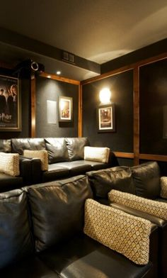 This fantastic home theater has two sets of sofas and two loveseats on different levels. The room is decorated with film posters.