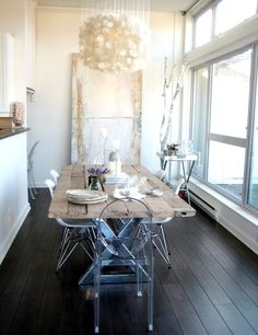 Rustic meets modern - reclaimed wood table with lucite chairs and sleek, dark floors.