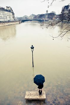 A girl with an umbrella smokes a cigarette on a bench surrounded by the water of the Seine River, in front of a drowned streetlight, Paris, 2010. Photo by Guillaume Gaudet.