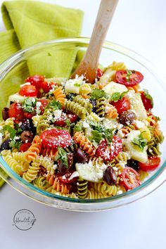 Greek pasta salad is a tangy and fresh dish that is perfect for a picnic or potluck. Tomatoes, basil, olives, cucumber, rainbow rotini and feta cheese.