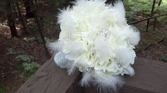 Cream rose, white feather, and brooch bouquet.