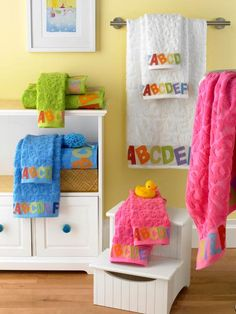 Bright colors pop on a white background. The colorful ABC six-piece towel set from Kassatex Bambini for Wayfair, works perfectly against the porcelain sink and white storage units. The step stool, which is perfect for kids to reach the sink, can hold bath toys, soaps, bubble bath and other products.