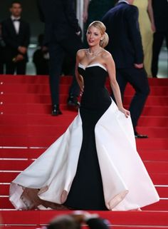 Blake Lively on the red carpet at Cannes Film Festival wearing a stunning strapless, multi panel black and white gown by Gucci, with her hair up and signature red lip.