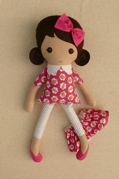This is a handmade cloth doll measuring 20 inches. She is wearing a sweet, fuchsia floral dress with gold accents, gold and white polka dotted leggings, and hot pink shoes. Her dark brown hair is worn in low, rounded ponytails and accented with a matching pink fabric bow. She is made from 100% cotton fabrics, wool blend felt, and polyester fiberfill. Her seams are triple stitched and she is firmly stuffed with Polyfil.   Please hand wash or machine wash on gentle cycle. Lay flat to dry…