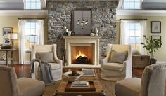 Harmonious Living Room Design Featuring Four Chairs With Grey Cover And Low Wooden Coffee Table In Front Of White Fireplace With Stone Wall Surround Ideas. Many benefit when applied this stone into our home. Beside the durability. this stone is water resists also stain free along with natural textures and colors give you a natural decoration on your indoor area likes fireplace and staircase also landscaping as well as table-tops and back-lit wall and sinks ideas.