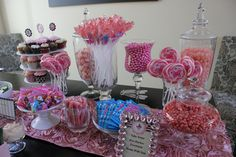 Pink candy buffet in apothecary jars sets the decor for a Sip & See party and also serves as favors for guests.